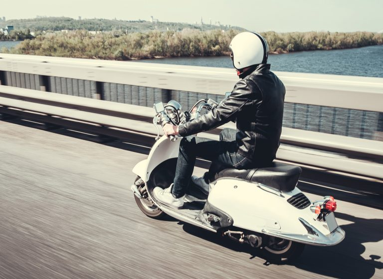 Guy in leather jacket and helmet is riding on scooter through the city bridge